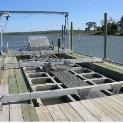 This is a floating, paddlewheel operated upweller. The paddlewheel pushes water through the upweller containers (instead of cylinders they are rectangular boxes) in the same manner as onshore upwellers that utilize pumped water from an adjacent water source.